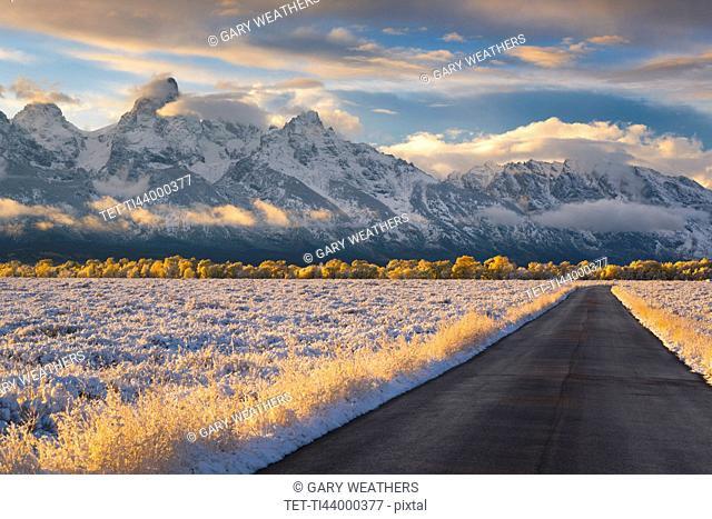 USA, Wyoming, Country road and Teton Range at sunset