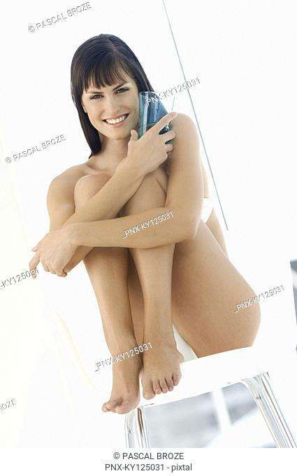 Young smiling woman in underwear sitting on a chair, holding glass of water