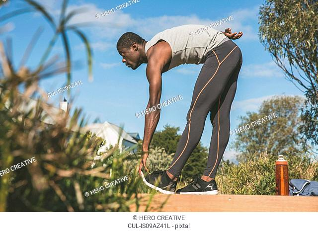 Man bending forwards touching toes, stretching