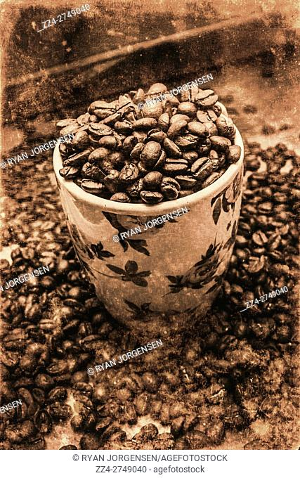 Ceramic mug full of coffee beans on table with scattered around beans. Old coffee house still life