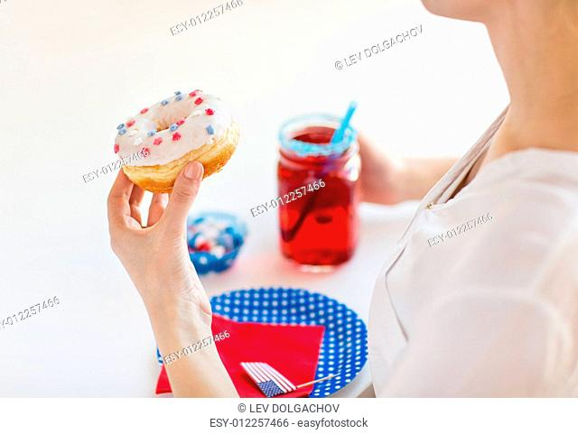 independence day, celebration, patriotism and holidays concept - close up of woman eating glazed sweet donut, drinking juice from big glass mason jar or mug and...