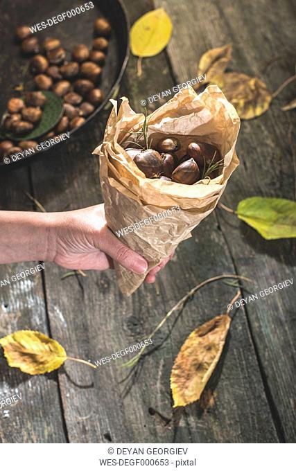 Woman's hand holding paper bag of roasted sweet chestnuts