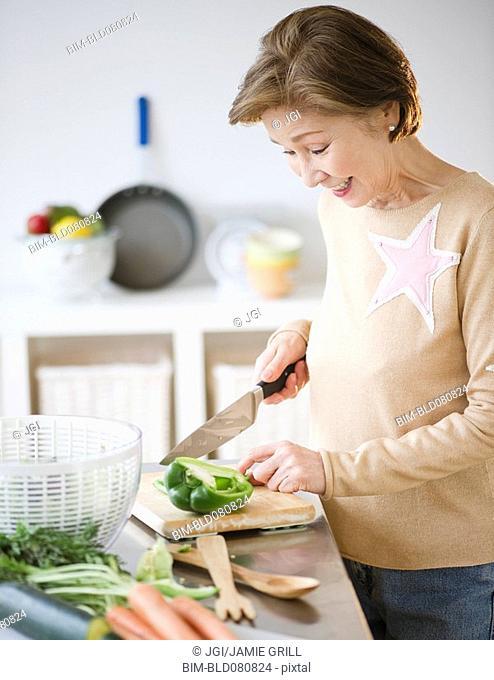 Japanese woman preparing vegetables in kitchen