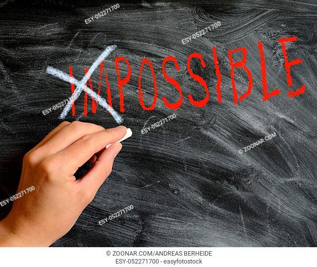 Hand writing on a blackboard Possible