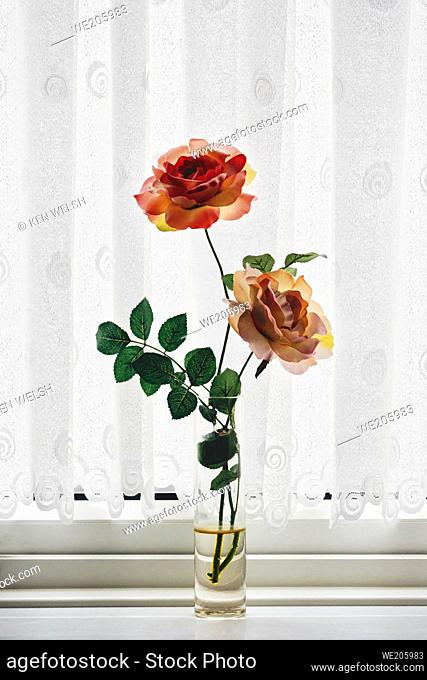 Plastic flowers in water in a vase on a window sill
