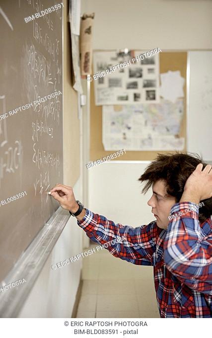 Caucasian student writing on blackboard