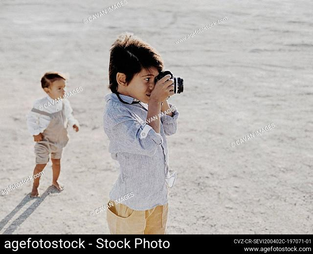 Kid takes photo with vintage camera as other kid stands in background