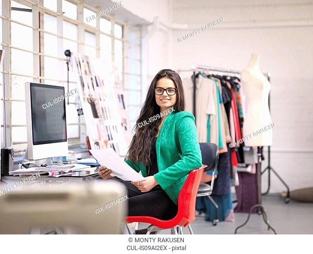 Fashion designer working at computer in fashion design studio, portrait