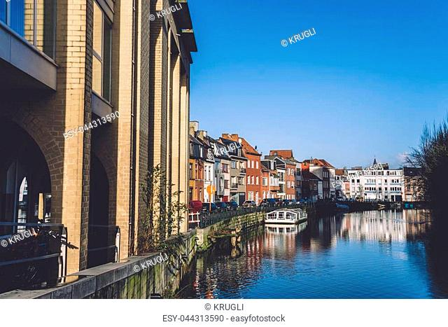January, 2th, 2017 - Ghent, East Flanders, Belgium. Portus Ganda marina with colorful belgian street, town houses and barges in docks reflected on the water of...