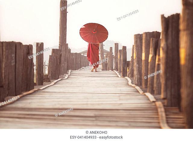 Novice walk on u bein wooded bridge in morning time, Mandalay city, Myanmar