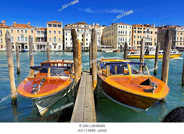 Wooden water taxi boats moored on sunny Grand Canal in front of architectural buildings in Venice, Italy