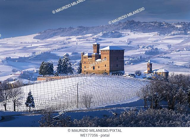 Grinzane Cavour, Piedmont, Italy View of the Castle, Unesco symbol, illuminated by an evocative beam of light, surrounded by marvelous hills and snowy vineyards