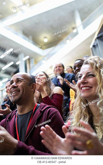 Smiling people clapping in conference audience