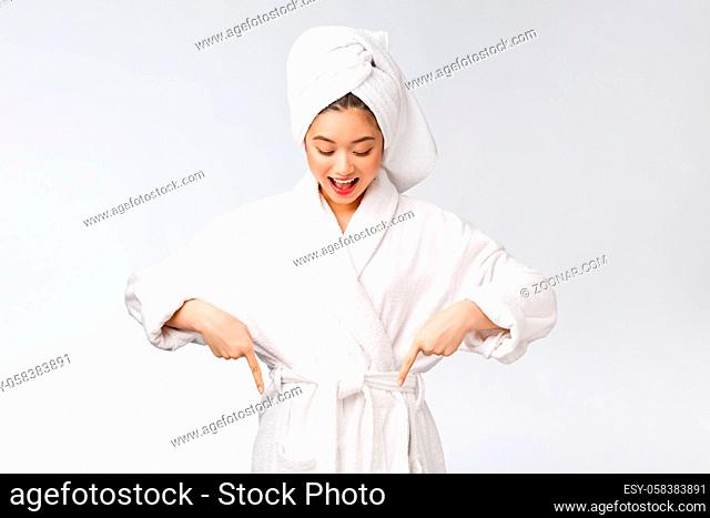 Beauty portrait of young woman showing and pointing finger to empty copy space, asian beauty in bathrobe