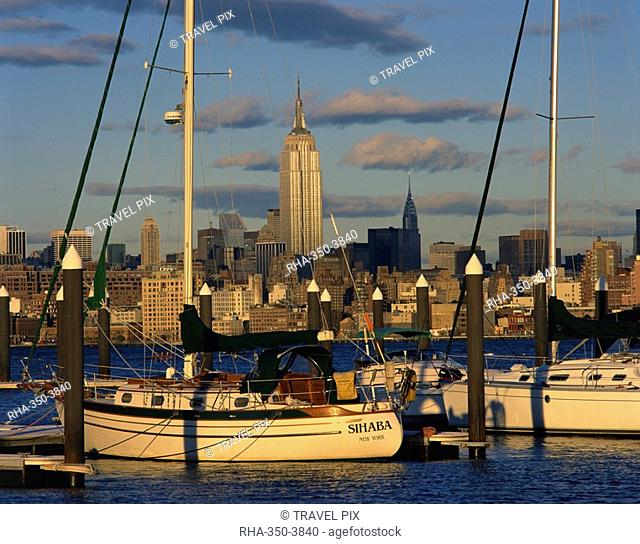 Boats in the harbour with the Empire State Building on the skyline in the background, in New York, United States of America, North America