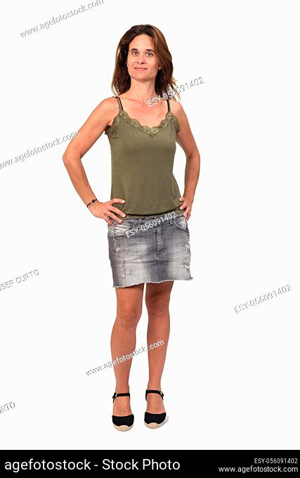 front view of the full portrait of a woman in a denim skirt on white background, hands on hip