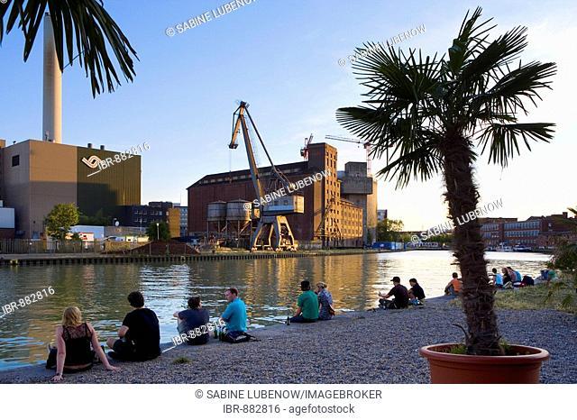 People sitting on the riverbank, evening mood at Kreativkai docks, Muenster, North Rhine-Westphalia, Germany, Europe