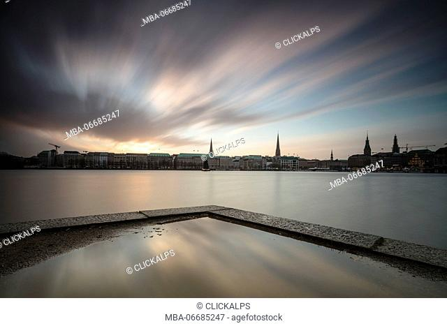 Clouds and lights of twilight on Inner Alster Lake with the Christmas Tree suspended in its water Hamburg Germany Europe