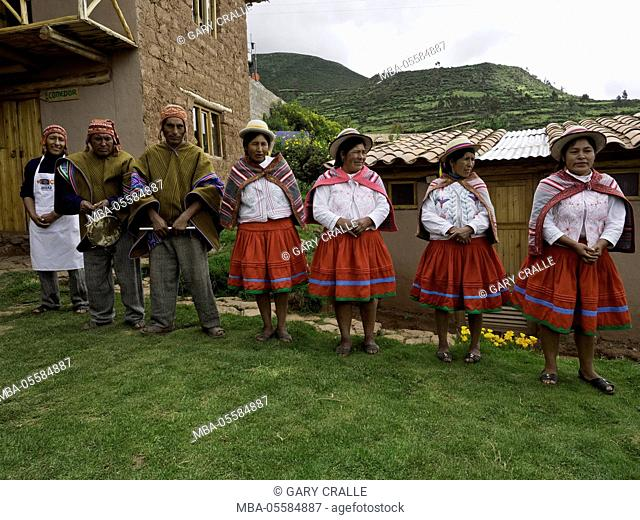 Quechua men and women wearing traditional clothes (and modern apron) greet visitors