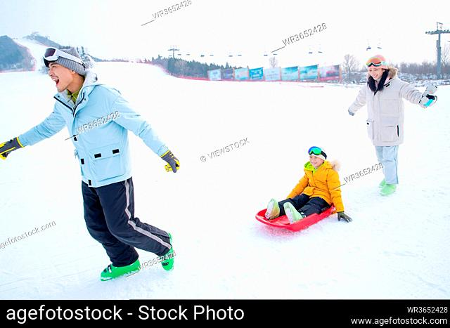 Parents and sitting in the snow ski son play skateboard