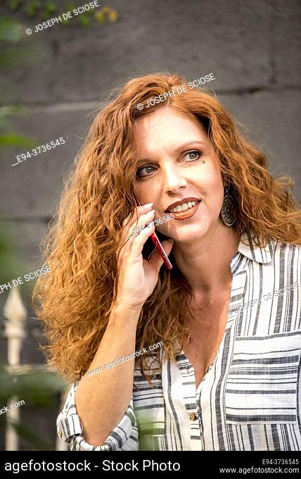 A beautiful 41 year old redheaded woman speaking on a cell phone