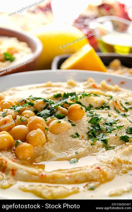 Fresh homemade Hummus in clay dish topped with olive oil, chickpeas and chopped green coriander leaves on stone table served with spices