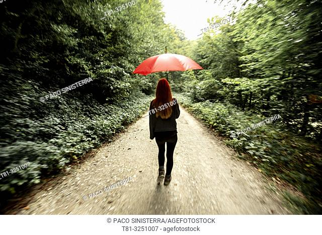 Girl walking through the forest with red umbrella, Navarra. Spain
