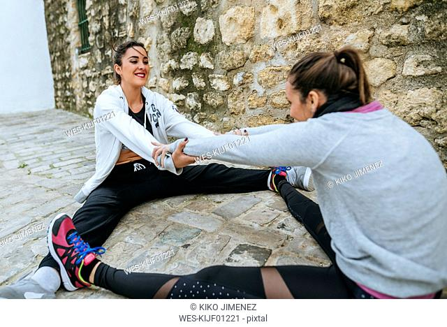 Two young women dong stretching exercises in the street