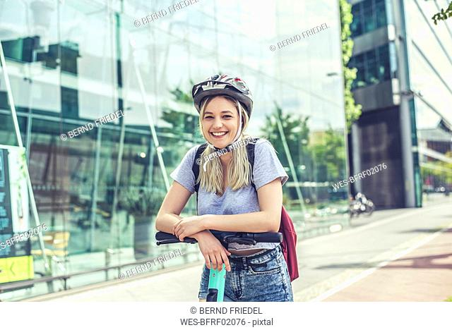 Portrait of happy young woman wearing cycling helmet leaning on handlebar of E-Scooter