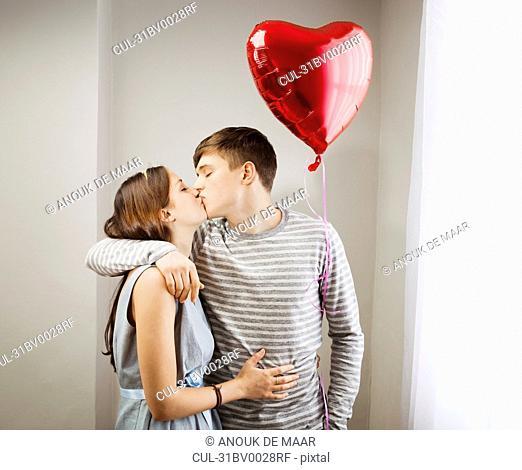Couple kissing,holding heart balloon