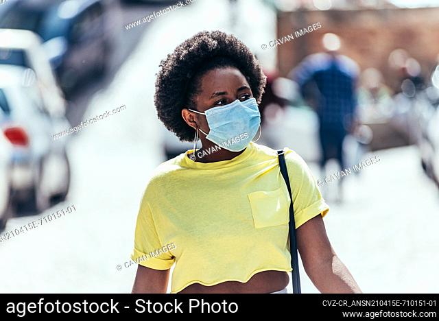 Black girl with face mask and afro hair walking through the city