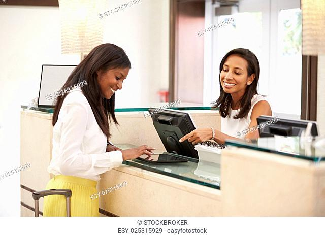 Woman Checking In At Hotel Reception Using Digital Tablet