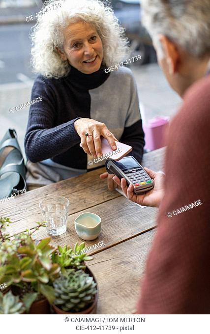 Woman using smart phone contactless payment at cafe