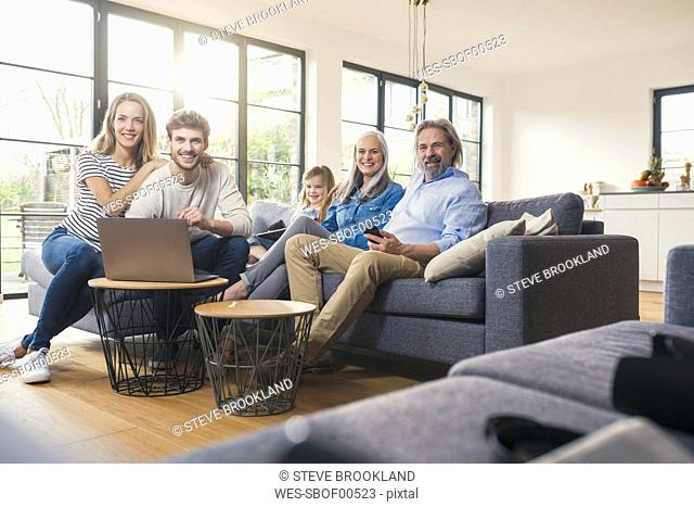 Extended family sitting on couch, using mobile devices