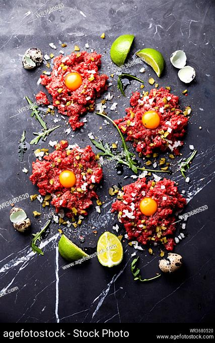 Beef tartare steak with pickled cucumber and onion on dark marble background