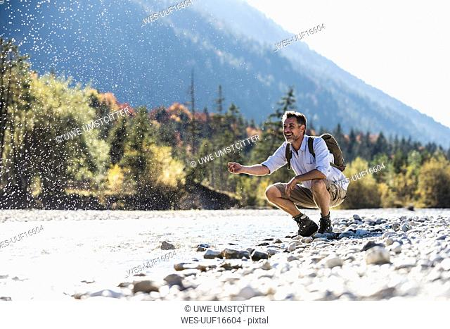 Austria, Alps, man on a hiking trip having a cooling break at a brook