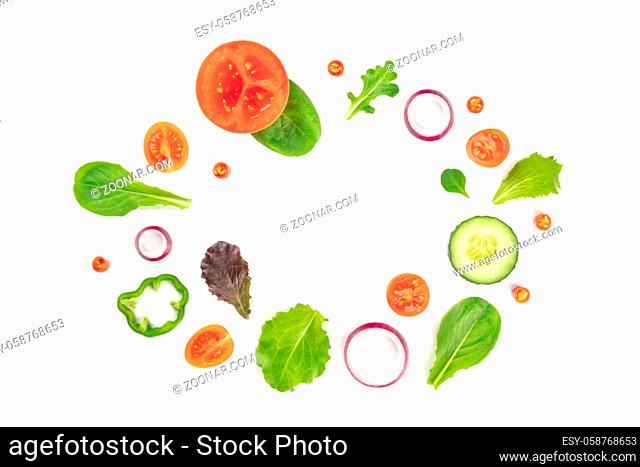 Fresh vegetable salad ingredients, shot from the top on a white background. A flatlay composition with tomato, pepper, cucumber, onion slices and mezclun leaves