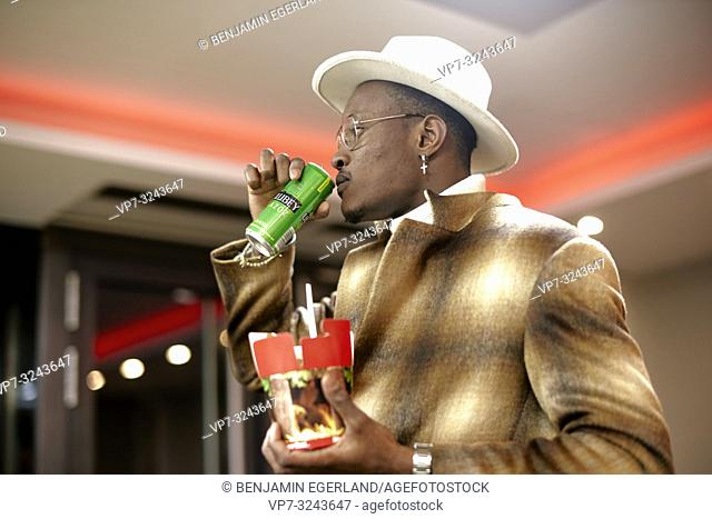 well-dressed stylish man drinking energy drink from tin while holding takeaway fast food doner kebab box, indoors, in Munich, Germany