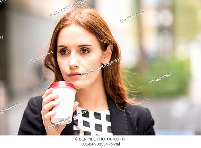 Portrait of woman holding disposable coffee cup looking away