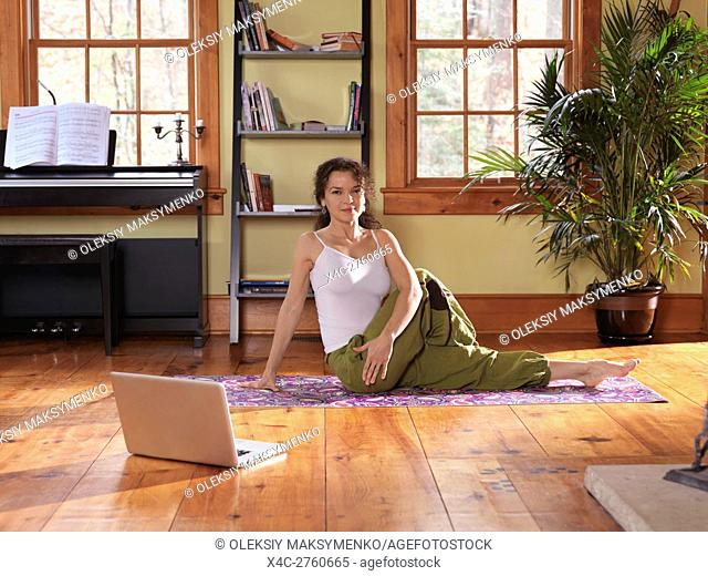 Smiling young woman practicing yoga postures at home in a living room on a bright sunny day