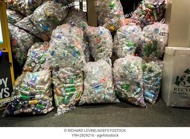 One day's collection of bags of cans and bottles await recycling in the vestibule of a drug store in New York