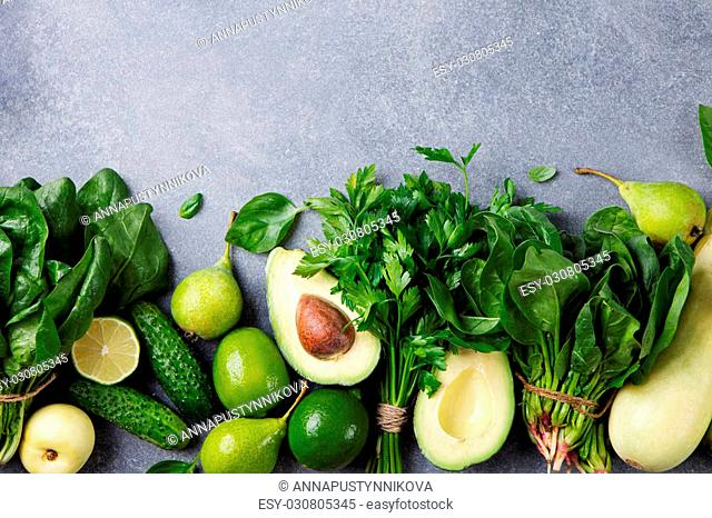 Green vegetables and herbs assortment on a grey stone background. Copy space Top view