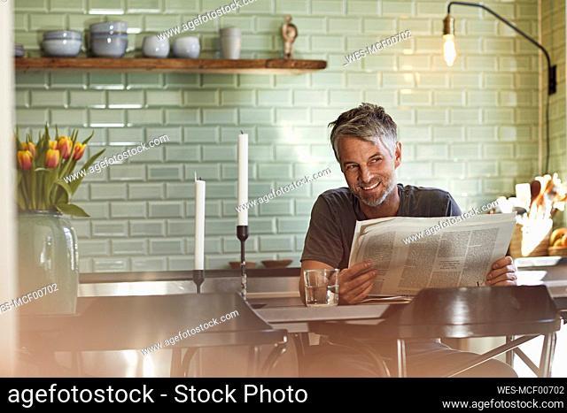 Smiling mature man sitting in kitchen reading newspaper
