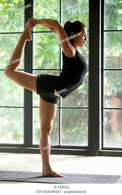 Young attractive sporty woman practicing yoga, standing in Natarajasana exercise, Lord of the Dance pose, working out, wearing sportswear, black shorts and top