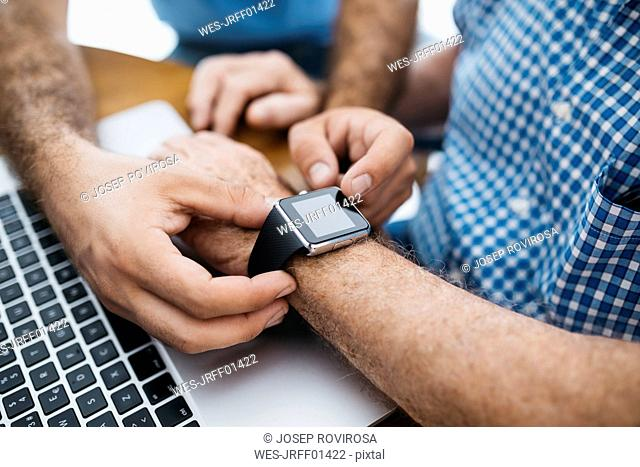 Adult grandson teaching his grandfather to use smartwatch, close-up
