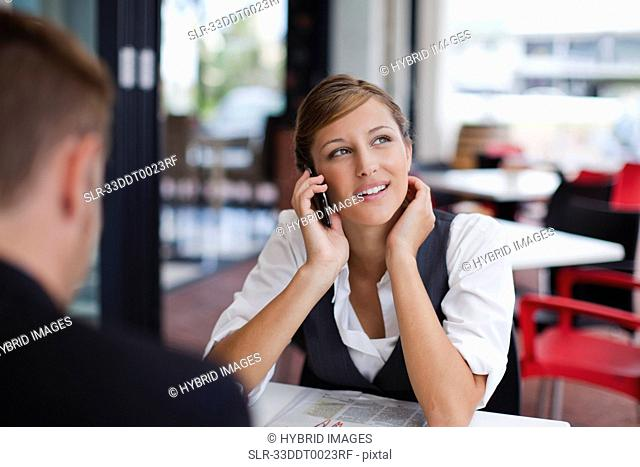 Businesswoman on cell phone at lunch