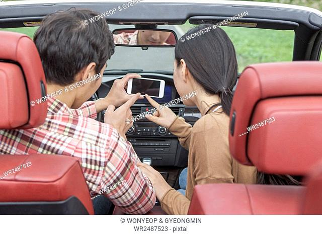 Back of young couple in a car using a smartphone