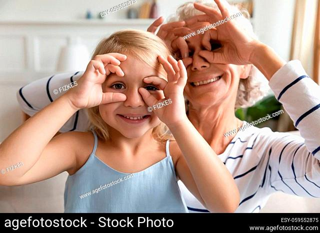 Close up funky old grandma small granddaughter with funny faces making binoculars with fingers like eyeglasses fooling around together at home