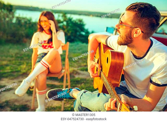 Couple sitting and resting on the beach playing guitar on a summer day near river. Love, happy family, vacation, travel, summer concept