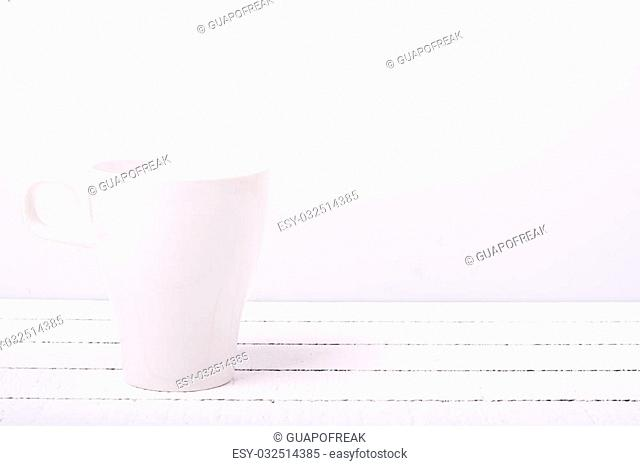 White coffee cup on a white wooden background